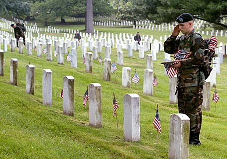 "ARLINGTON, VA - MAY 27: A member of the U.S. Army Infantry Regiment (The Old Guard), salutes after placing a flag on a grave stone at Arlington National Cemetary May 27, 2004 in Arlington, Virginia. An event called ""Flags In"" takes place before every Memorial Day weekend in honor of those veterans who have lost their lives. (Photo by Mark Wilson/Getty Images)"